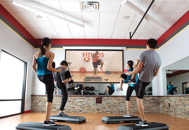 Virtual workouts via projection screens or large TVs have started to replace instructor-taught workouts at student housing developments.