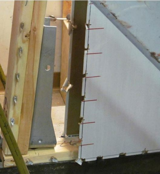 Sheathing tearout at the edge of a wall assembly sheatherd with ThermoPly Red duringAPA tests to evaluate shear resistance.