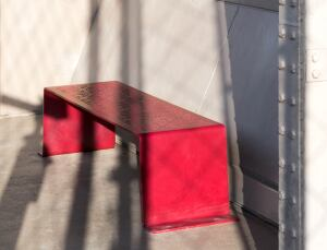 Metal benches are punched with a pattern resembling the Eiffel Tower's iron latticework.