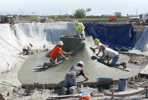 "All hands on deck: The crew from Seattle-based Grindline Skateparks work the trowels on a ""spine"" — two ramps stitched together — at the Spring Park Skatepark in Houston, Texas."