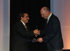 Bill Palmer receives a congratulatory handshake from Luis Garcia, ACI president