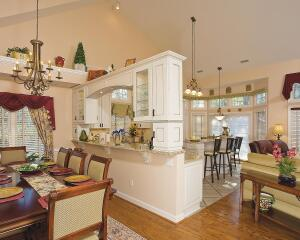 The clients, owners of a Raleigh, N.C., townhouse, wanted to open the kitchen to the living room and dining room to improve traffic flow and to create a more cohesive space. The homeowners showed remodelers David and Peggy Mackowski of Quality Design and Construction a photo of an arched opening they liked, and they wanted to use that as the design inspiration for delineating the dining room and kitchen spaces.