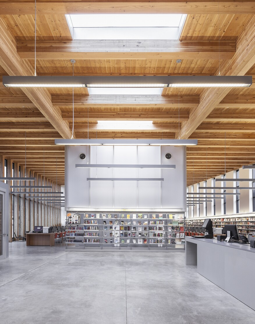 The addition and its material palette—the Douglas fir ceiling and beams, polished concrete floor, skylights, and expanse of glazing—all take their cues from the existing building.