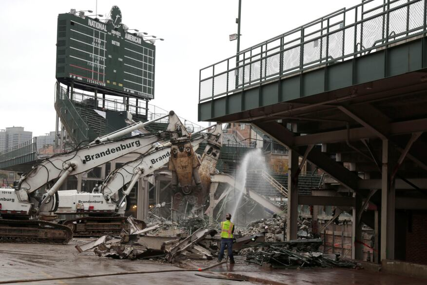 Construction crews begin to demolish the outfield walls at Wrigley Field in Chicago for the ballpark's $575 million renovation project.