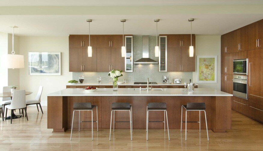 Sleek kitchens feature an off-white and gray backdrop accented with cherry cabinets and French limestone counters.