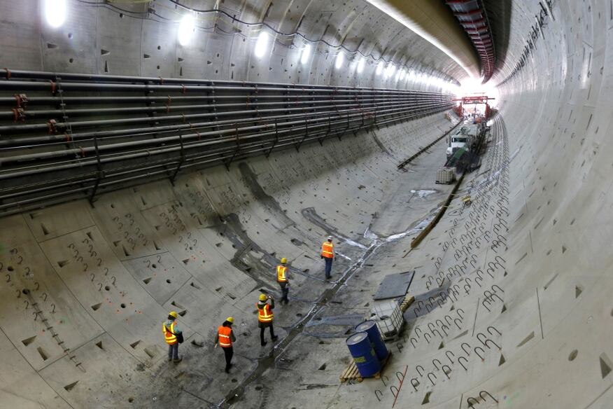"""Visitors walk through a five-story tunnel being constructed to replace the Alaskan Way Viaduct in Seattle. Progress on the two-mile tunnel that will move State Route 99 underground stalled in December after the tunnel boring machine had to be shut down for repairs, but work on tunnel walls and other structures continued. The tunnel topped a list of """"11 highway boondoggles"""" that shouldn't be constructed, in a report released yesterday by the U.S. Public Interest Research Group Education Fund. [The Seattle Times]"""