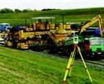 """Stringless paving technology has been dreamed about for a long time,"" said a January 2005 article. The first entrant in the U.S. market uses three robotic total stations to guide the direction of travel and produce pavement within a hundredth of a foot of specified elevations."