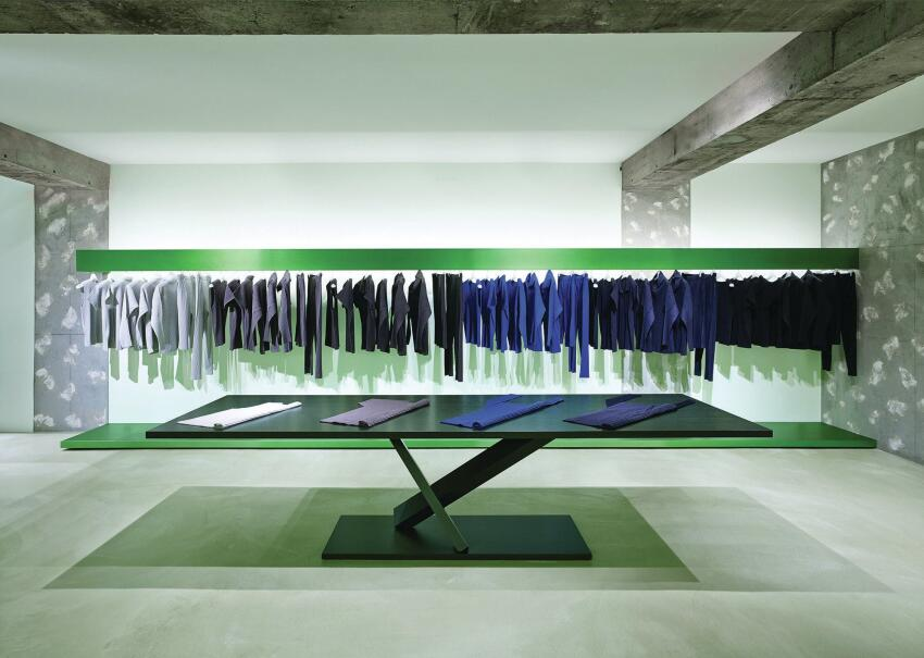 The lower level features green displays. Yoshioka's office designed the steel tables with the angled legs for Italian furniture maker Desalto. Known as Element, the series complements the sculptural, freestanding steel clothing racks deployed throughout.