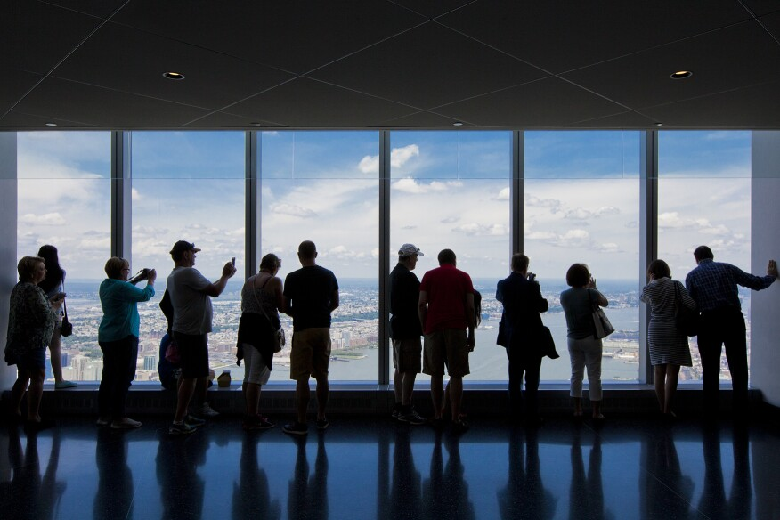 Tourists view New York from the One World Trade Center observation deck.