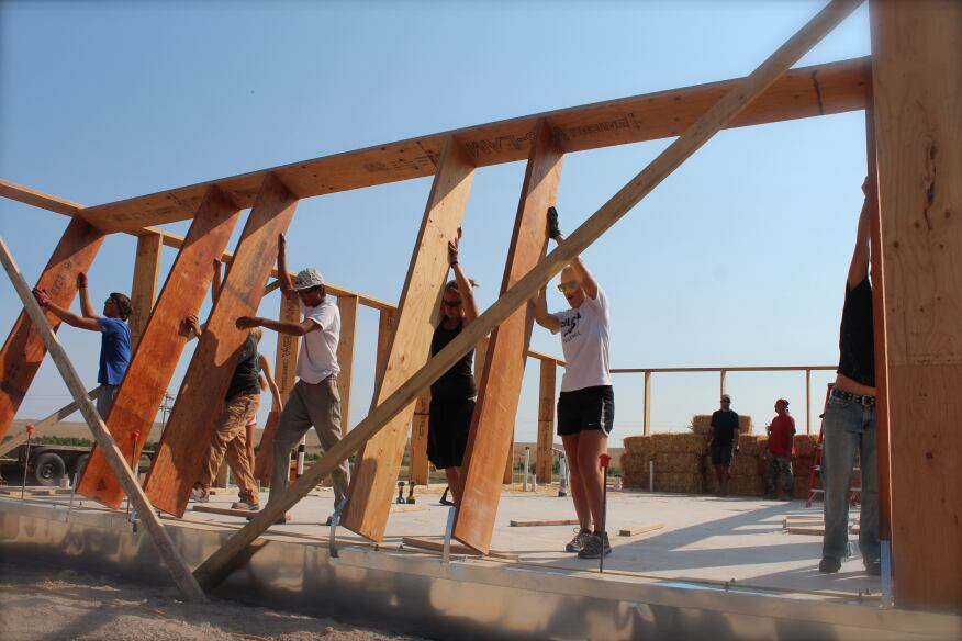 Students tilt up the frame to the protype house.