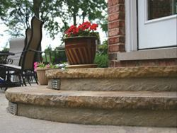 Cantilevered radius steps use Butterfield Color's formliner to create texture. A soft integral color, Lannon Stone, is the base for a rich finish with multiple colors of stain and sealer. Contractor: Don Garceau