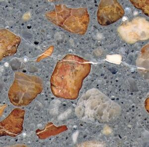 Cross-section of concrete cracks caused by alkali-reactive chert and strained quartz. Filling the cracks and air voids is white alkali-silica gel.
