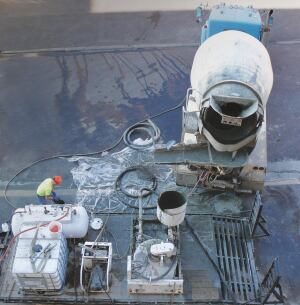 Geotechniques transported cellular concrete equipment to the site on a trailer. Foaming agent contained in the cube-shaped tote (foreground left) was mixed with water in the foam generator (cylindrical tank left), then foam was added to ready-mix in the transit mixer. After mixing, the cellular concrete was discharged into the hopper of the hydraulic pump (foreground right) to be pumped into the building.