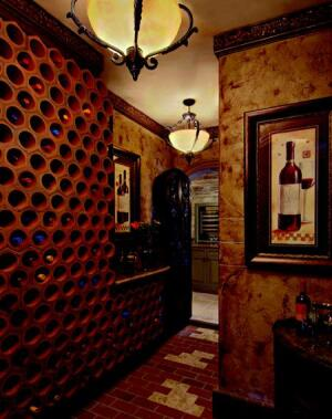 VINTAGE VAULT: A wine cove across from the dining room makes practical use of an odd-shaped  space underneath the main staircase. The honeycombed storage cubbies are  fashioned from sections of terra cotta pipe.