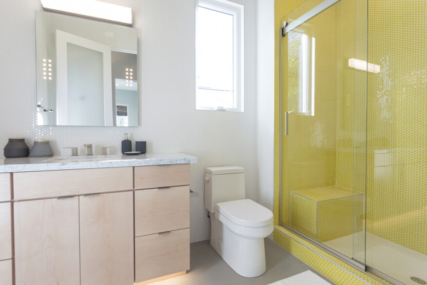 This bathroom in the large home gets its modern aesthetic from clean lines on all the fixtures and finishes, including Gerber's Wicker Park toilet.