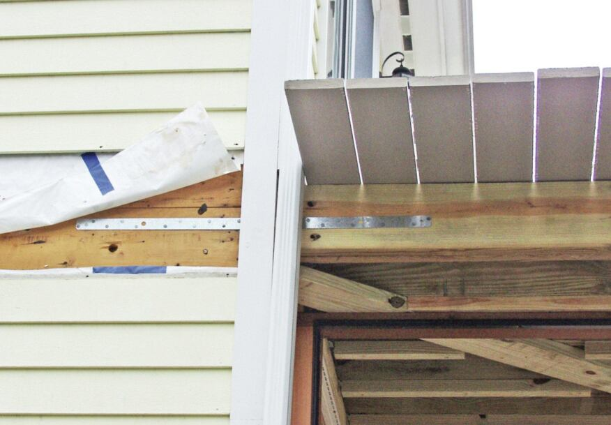When the deck framing is aligned with the house framing, a simple metal strap can provide sufficient strength to meet lateral load requirements. On existing construction, the siding and sheathing must be temporarily removed to gain access to the framing.