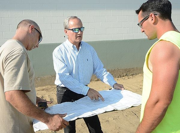 Building plans: Mike Giovanone (center) discusses the distribution center with two contractors.
