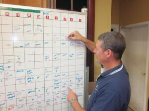Steve Taylor moves employees into position on a magnetic whiteboard Gantt chart that helps him schedule employees for multiple projects weeks at a time. The method helps shave time off projects.