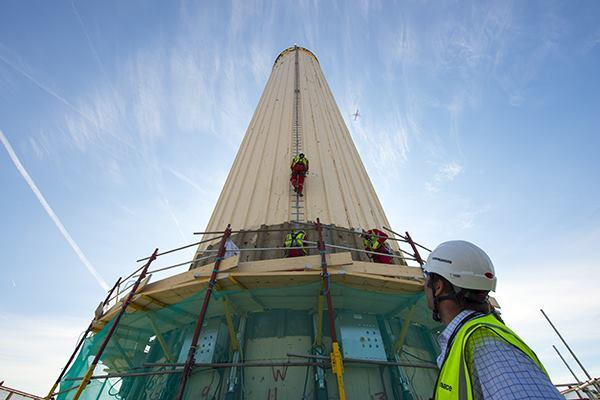 Work begins to remove the four chimneys from London's Battersea Power Station, which will then be rebuilt.
