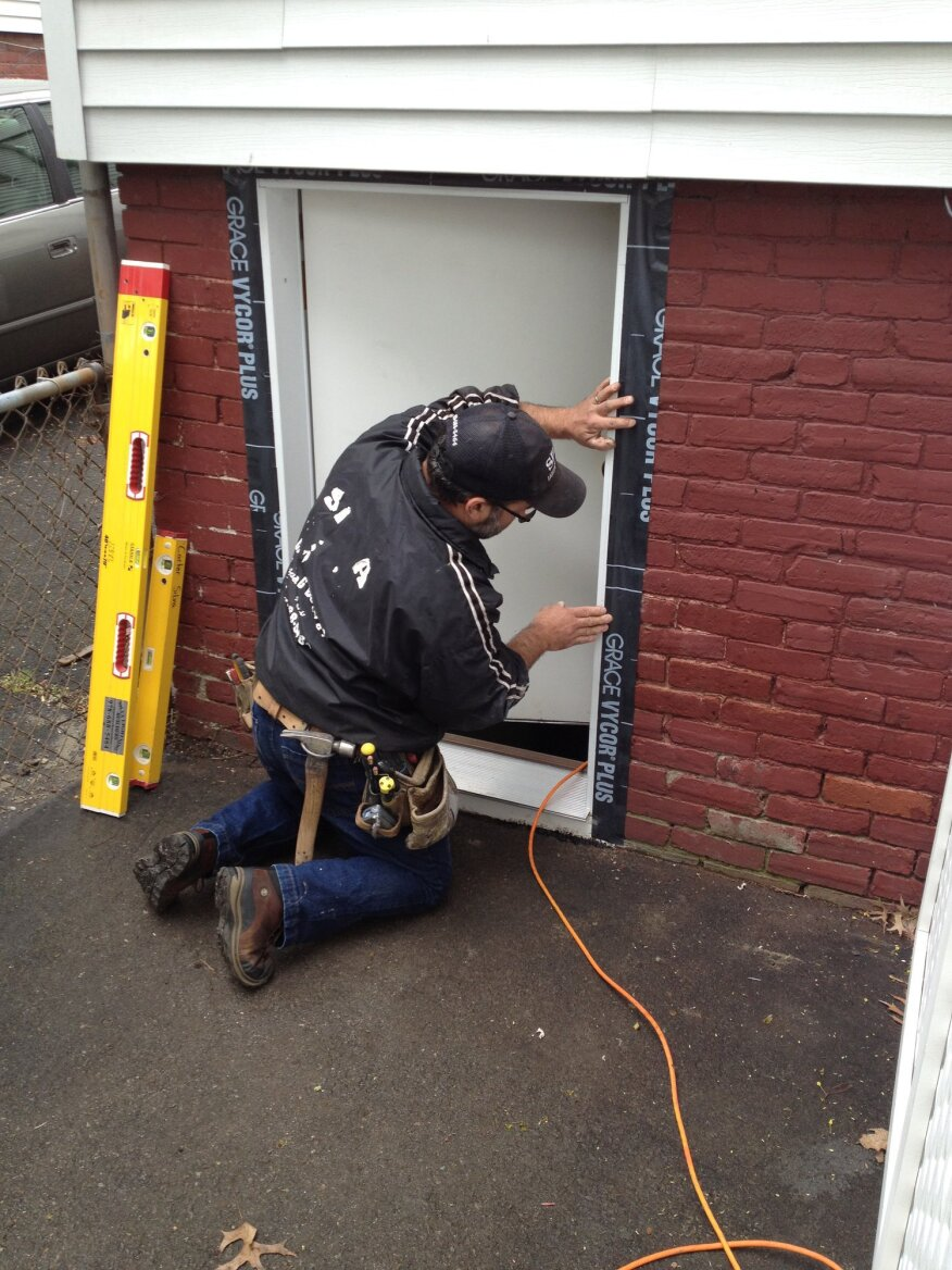 Self-adhered flashing tape weather-seals the gap between the door jamb and the brick.