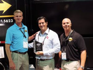 Company owners, Sam Petersen and Casey Hardee, presented John Davis, Vice-President of Heil of Texas, with a personalized trophy and a Petersen Industries' logo sign at the recent Waste Expo held in Las Vegas, Nevada.
