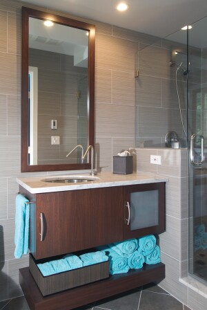 """Designer Mariette Barsoum says that frameless glass is the best solution for a smallspace shower. """"The less the better,"""" she says. """"There are a lot of other textures in the room, and we did not want the shower to be a focal point."""" For the shower floor, she chose smaller 2-inch-square versions of the wall tile, but added bright touches of blue, red, and green using glass tile inserts."""