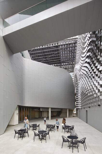 One of the most striking features of Morphosis's design is the eight-story sunscreen that shades the building's two internal façades. The firm used computational scripting to determine the final geometry. Over the better part of a year, in-house designer/programmers input the parameters that created the undulating and dynamic surface. The scripting program responded to inputs such as the curvature of the classroom building and the location of the elm tree in the fifth-floor courtyard.