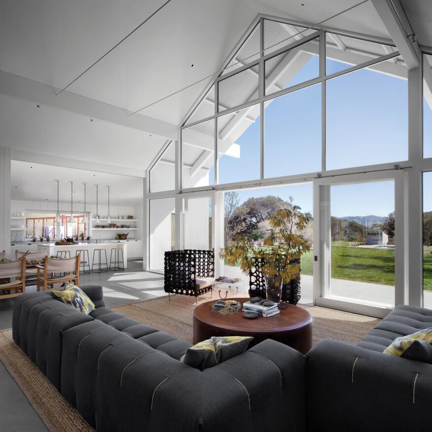 Living room with view of kitchen and adjacent meadow.
