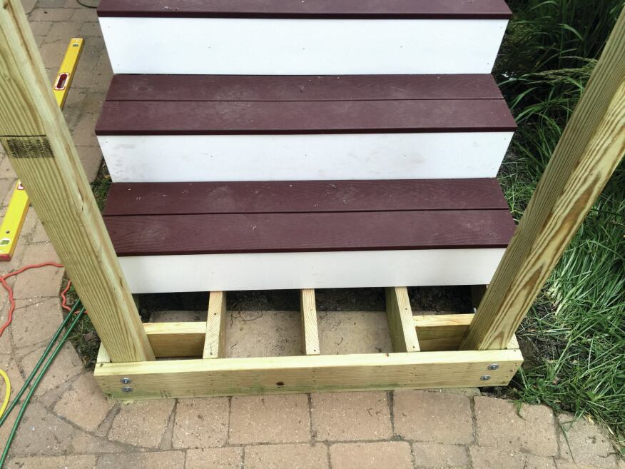 Stair stringers rest on a concrete pad and are fastened to the 2-by subriser and blocking with structural screws. The posts are then through-bolted to the assembly.