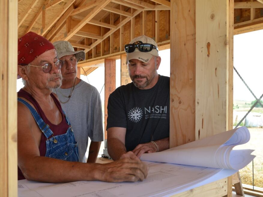 Lenny Lone Hill (left), with Oglala Lakota College, and Rob Pyatt (right), with the University of Colorado at Boulder, working inside a prototype straw-bale house that's being built by the Native American Sustainable Housing Initiative.