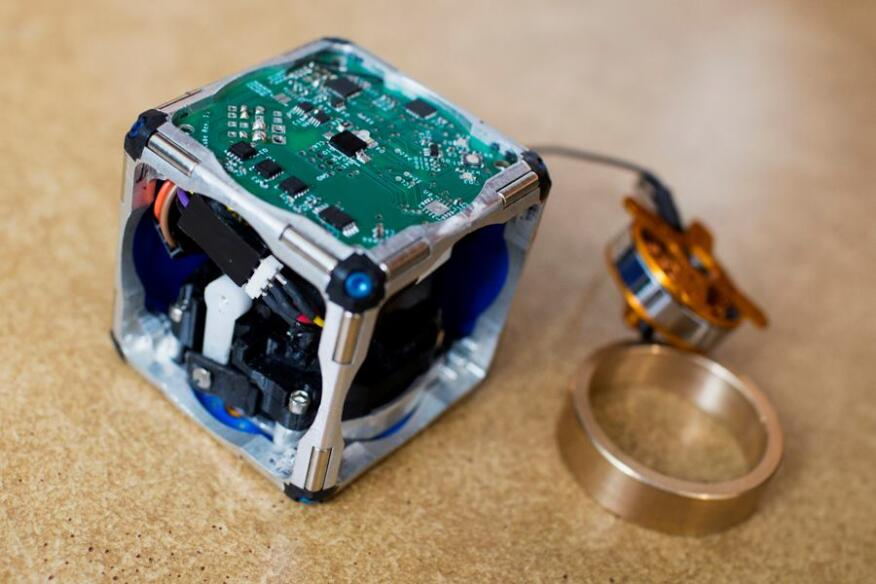 A prototype of a new modular robot, with its innards exposed and its flywheel — which gives it the ability to move independently — pulled out.