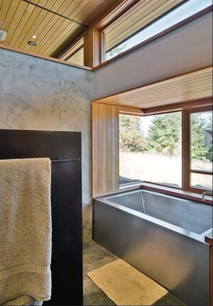 Waterproof plaster veneer gives the walls of the bath texture and random movement. Such visual tricks contrast nicely with the vertical-grain woods Prentiss speced.