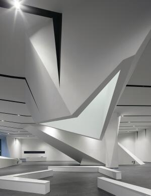 A skylit atrium extends through the building, terminating in an articulated aperture over a seating area in the ground-floor gallery.