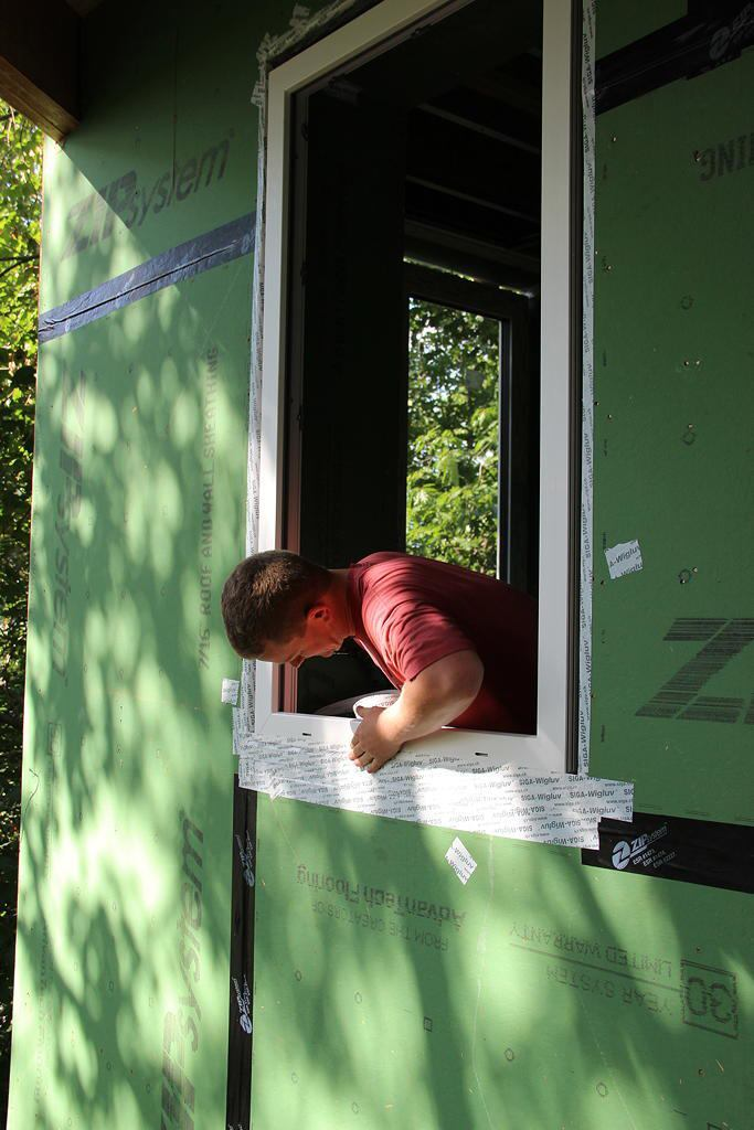 A crew member tapes the exterior window edge to the wall sheathing after the window is placed.