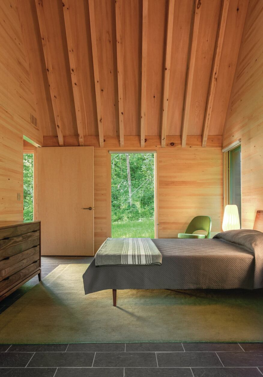 In the bedrooms, the forested site is visible through windows from Marvin Windows and Doors. The simple furnishings include beds from Design Within Reach and dressers from Arbet Design.