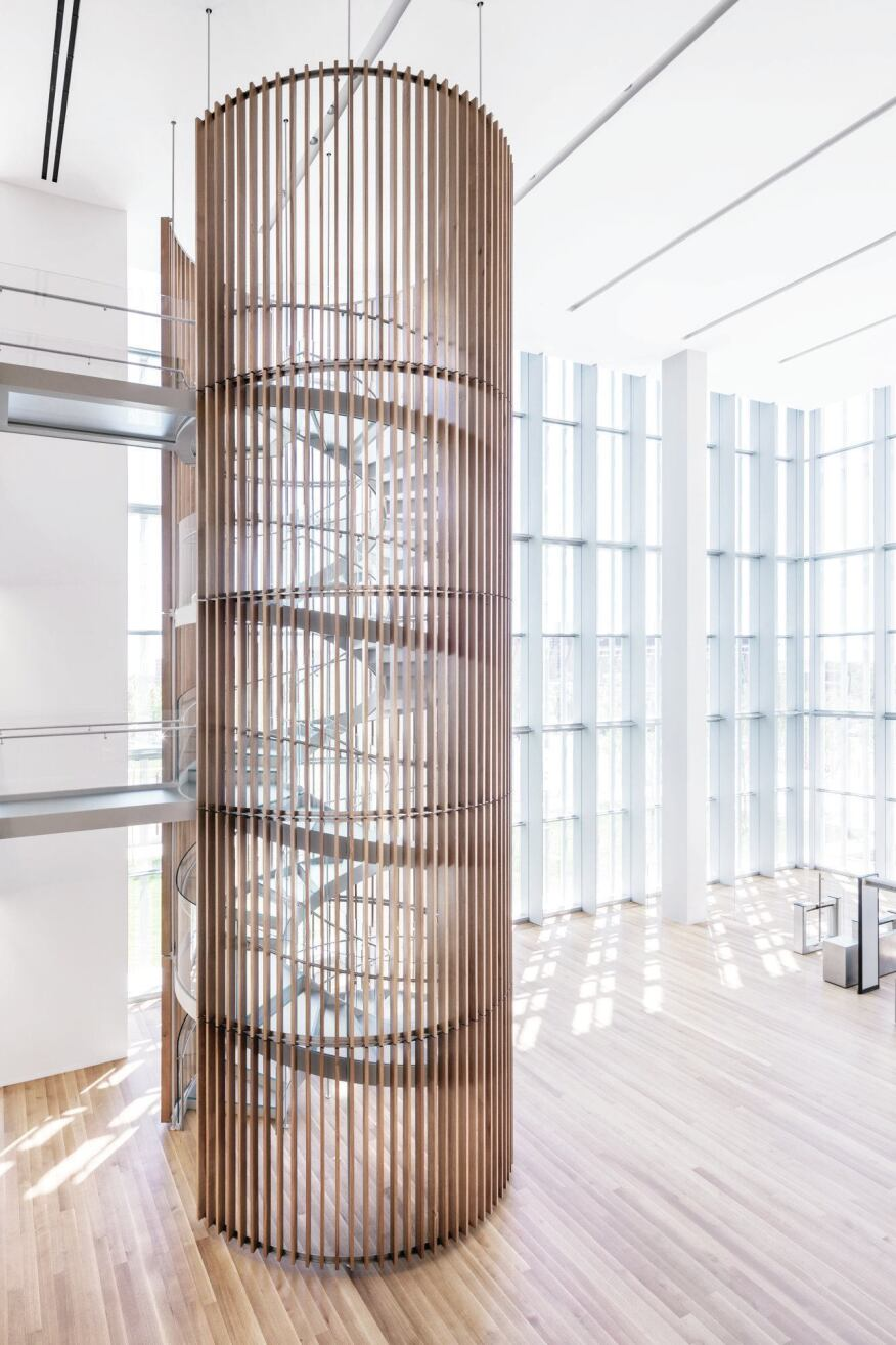 The lobby is a triple-height, light-filled volume. A spiral staircase, clad in wooden slats, provides circulation for those who do not want to wait for the elevators at the core of the building.