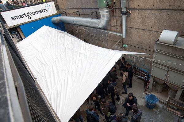 Smartgeometry participants and attendees mingle on the lower level of the Wates House at the Bartlett, UCL Faculty of the Built Environment in London. As the fabrication and 3D printing studio, the lower level of the facility saw a frenzy of actvity of a different kind in the days leading up to the April 19 exhibition.