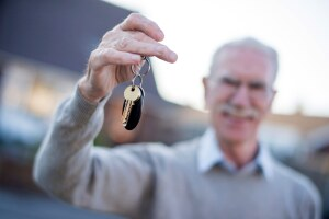 Happy in deed, a new retiree homeowner, takes over possession of his house keys.