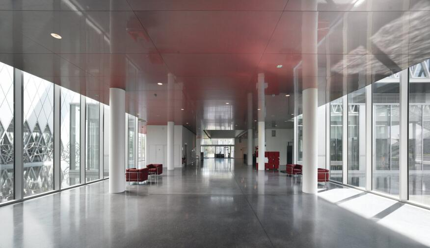 Inside the glazed structure, polished floors and metal ceilings also reflect light deep into the floor plate. Corridors offer sight lines through the building, here, to the public entry.