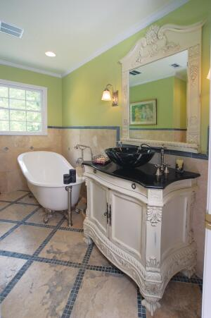 The womanís bath, one of five bathrooms in the home, offers a tranquil, furnished retreat.