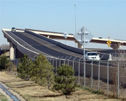 The State Highway 58 Flyover Ramp bridge features curbed precast concrete girders and the longest span of constant-depth precast concrete U-girder construction in Colorado. The project demonstrates the flexibility of precast U-girders to achieve complex geometries and long spans.