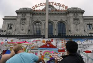 DENVER, CO - JULY 26: Visitors are encouraged to paint on a paper mural outside the station. Denver Union Station hosts a public event for their grand opening celebration featuring food trucks and live music on Wynkoop Street and free tours of the building. (Photo by Kathryn Scott Osler/The Denver Post)