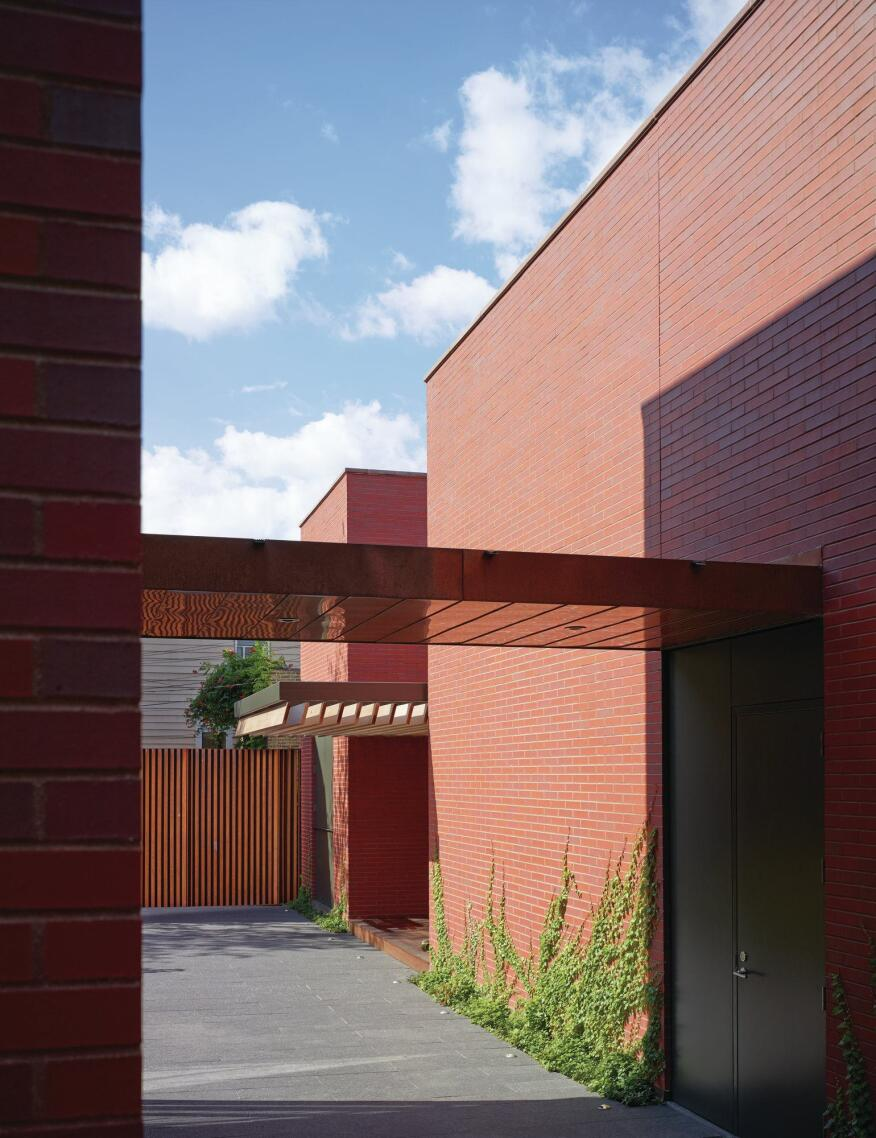 At the rear of the site, a free-standing garage is outfitted with an outdoor dining area, which is shielded by a slatted canopy. Black granite pavers create continuity between the exterior landscape and the interior, where the same material continues in the hallways.