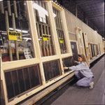 A Marvin Window and Doors employee checks the width of a new wall of windows being prepared for sale.