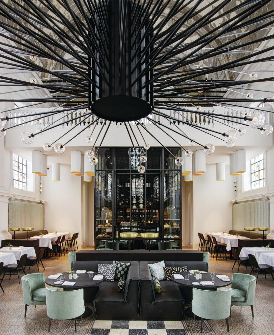 "The restaurant's main lighting feature is the 30-foot-wide by 40-foot-tall chandelier with 150 black-lacquered steel rods outfitted with a crystal globe at each rod's end. ""The globe[s] had to be really well thought out in order to bring the [desired effect] out,"" PSLAB founder Dimitri Saddi says. ""We did many tests on proportions and also weight, because the crystal added weight at the end of the 5-meter (16-foot) rod. We did four different mock-ups of the glass shades."""