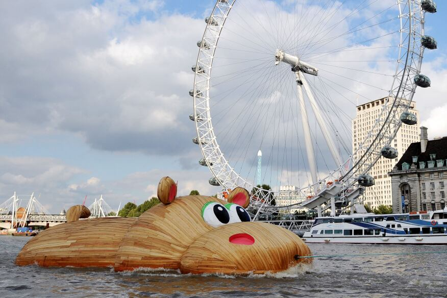 The 'HippopoThames' sculpture is towed past the London Eye. Florentijn Hofman, a Dutch artist known for his giant Rubber Duck project, designed the 69-foot-long hippo for the River Thames. The artwork was inspired by research from the National History Museum that found hippos once occupied the river.