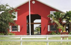 Tilt-up construction was chosen for the Sunlight Ranch Equestrian Barn because it offered storm resistance, cost savings, and quick construction. In order to complement surrounding structures, a panelized look was created using reveals and the facility painted a traditional stable red.