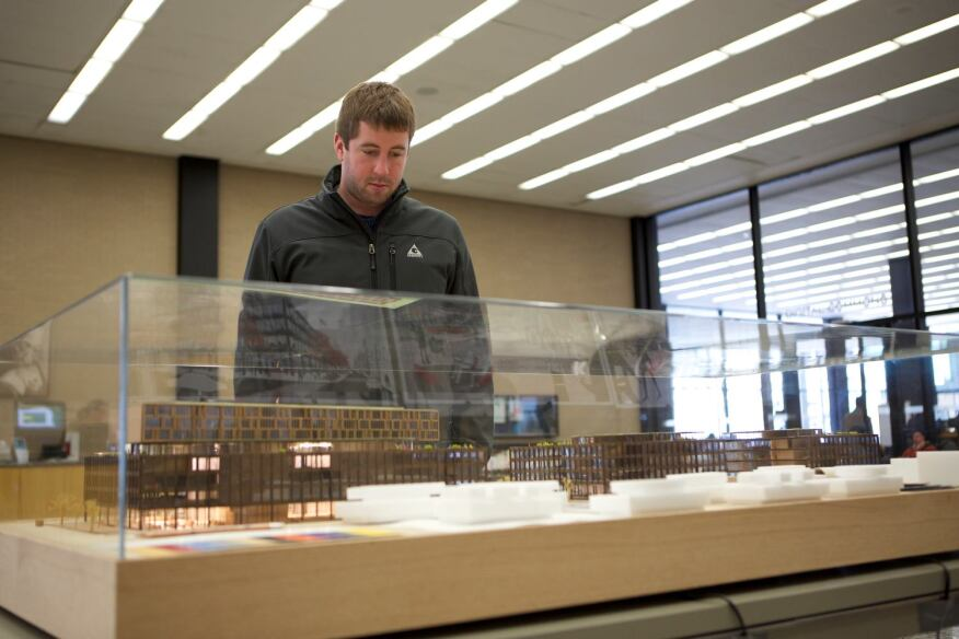 A visitor looks on at the Mecanoo/Martinez+Johnson Architecture proposal.
