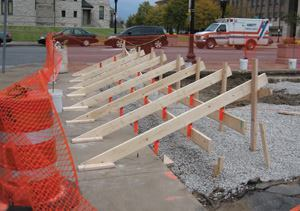 By cutting each successive stringer shorter, these concrete stairs will provide a good transition between the sidewalk sloping downward toward the front of the photo and the top step, which is set level. The end forms and bottom stringer have yet to be constructed.