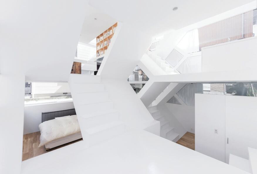 Scissoring staircases connect the split-level interiors, offering glimpses into the bedrooms, dining room, kitchen, and other spaces.